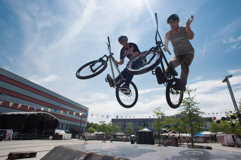 students jumping over a ramp with a BMX bike