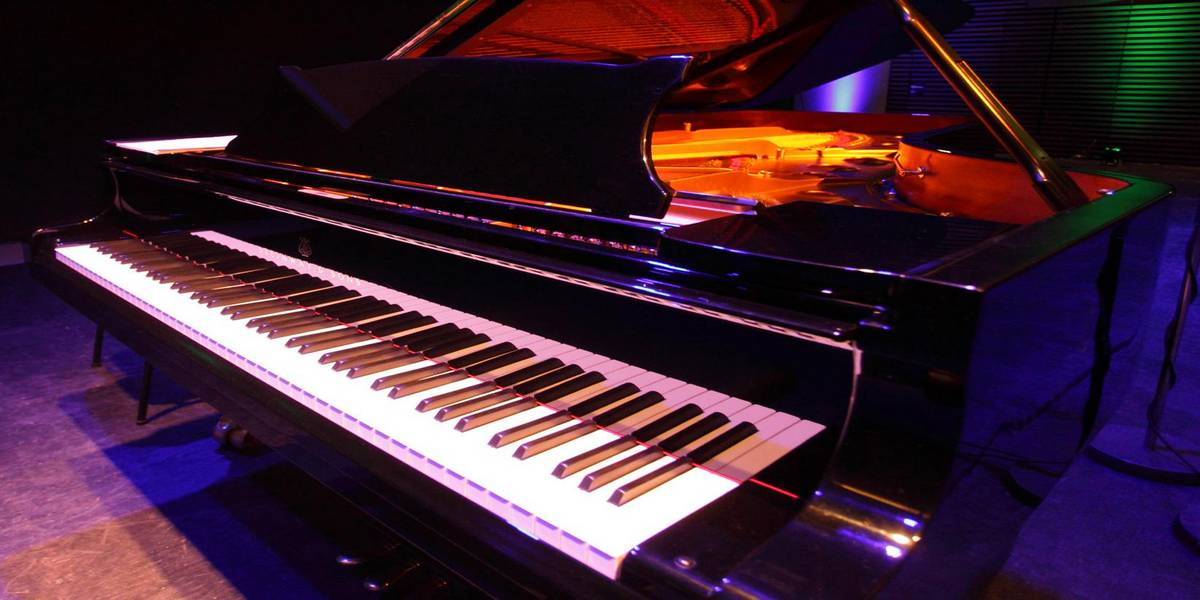 A concert grand piano illuminated in different colours - symbolic image for the bachelors programme in instrumental and vocal performance and teaching