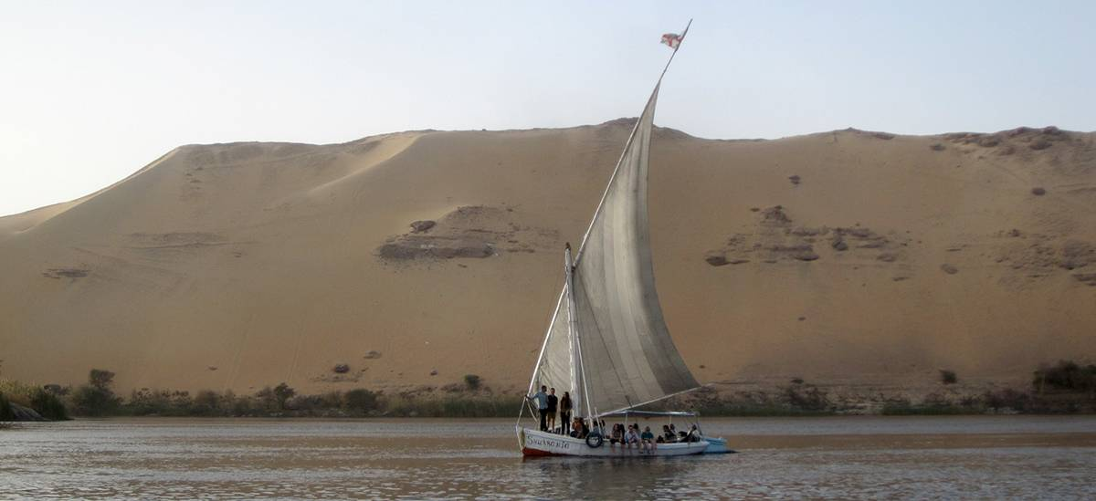A sailboat with students from the Heritage Conservation and Site Management master's program in front of a cliff covered with sand