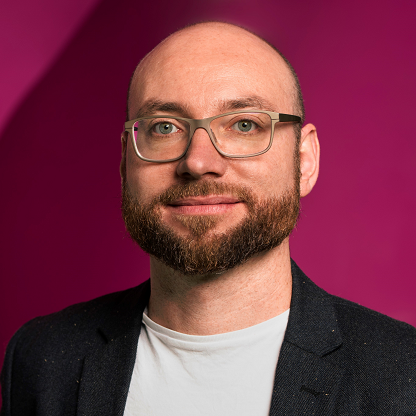 man with glasses in front of magenta background