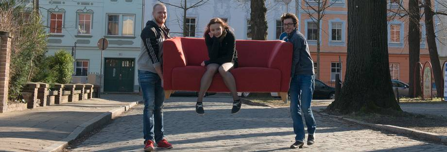 two students carrying another student through the Cottbus Old Town on a sofa