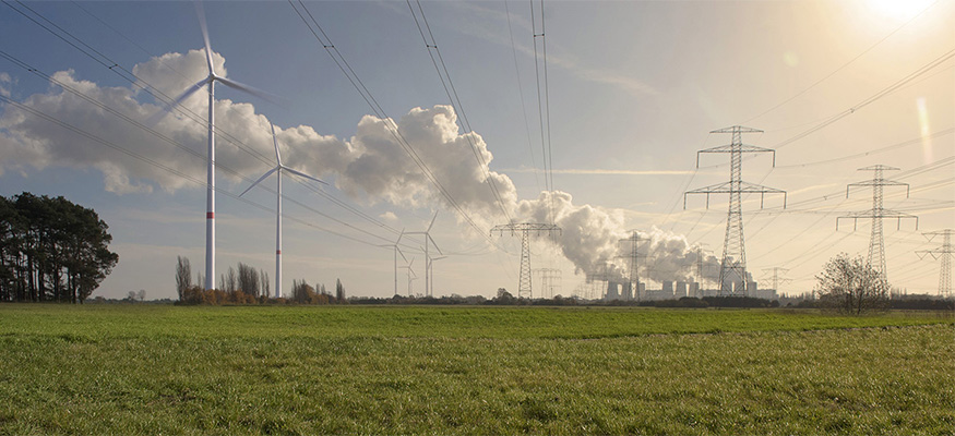 Green meadow with power lines, wind turbines and coal-fired power station in the background